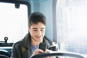 man texting and smiling on bus