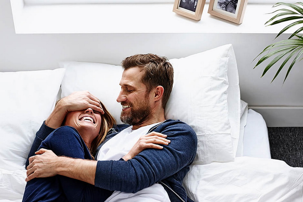 Young woman lying on mattress with man covering eyes of his girlfriend - Indoors