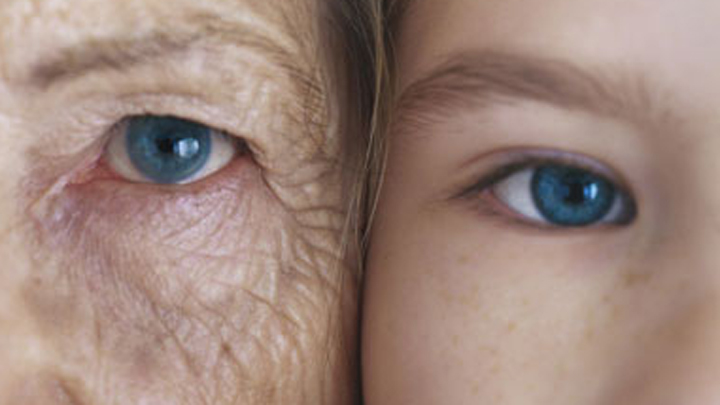 Girl and grandmother, cheek to cheek, close-up, partial view