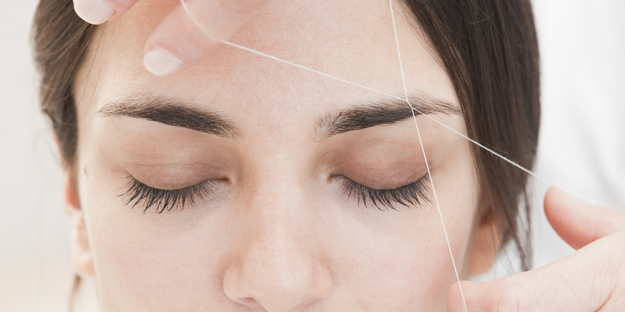 young woman having eyebrows Threaded